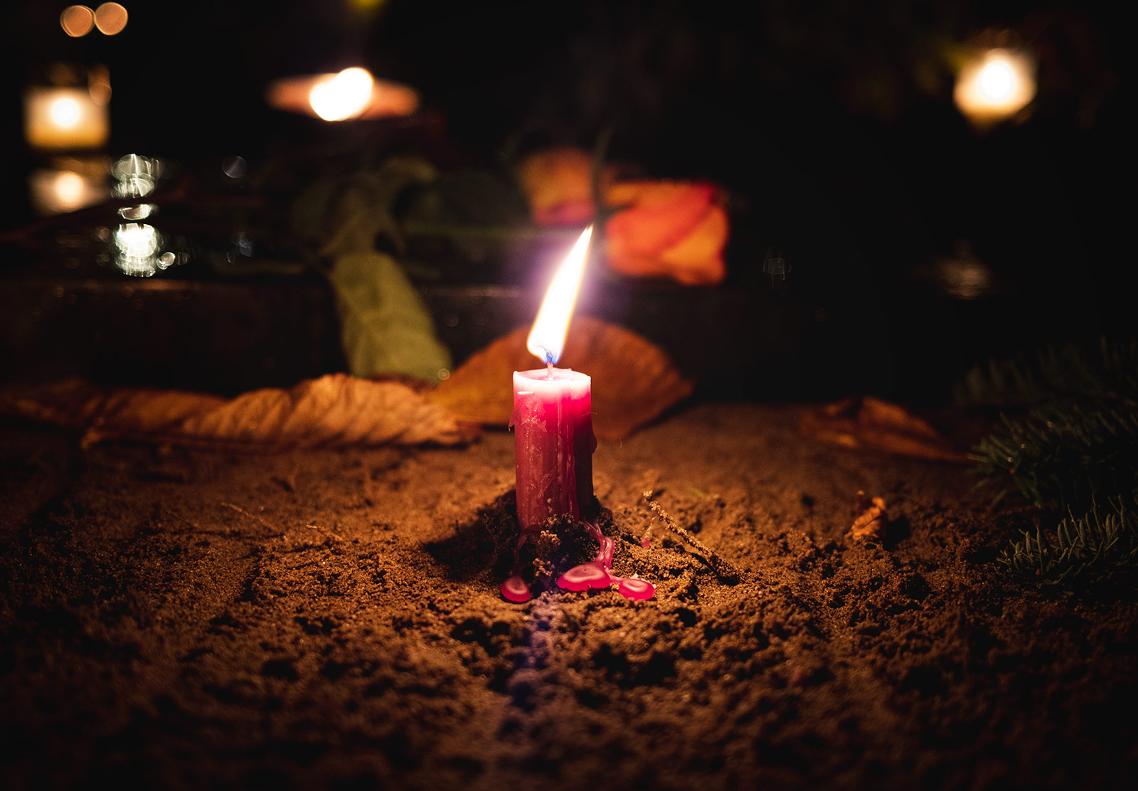 Red candle in the soil