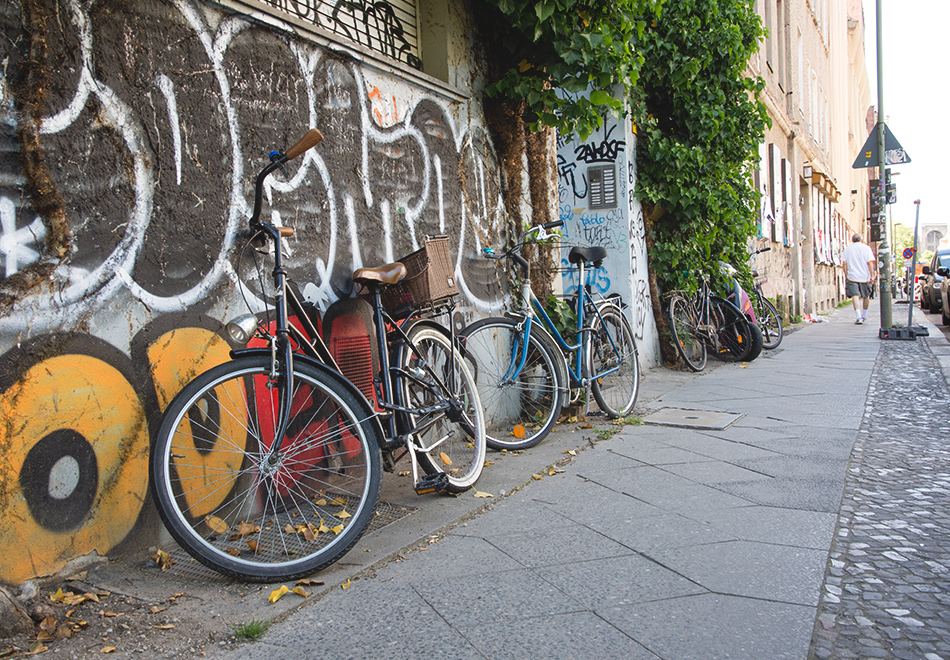Bikes resting against graffiti wall
