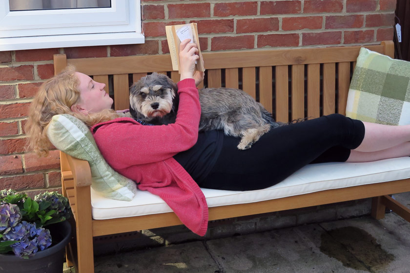 Laying on bench with dog