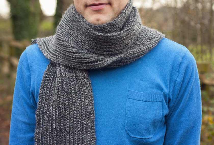 Man wearing a knitted grey rib scarf
