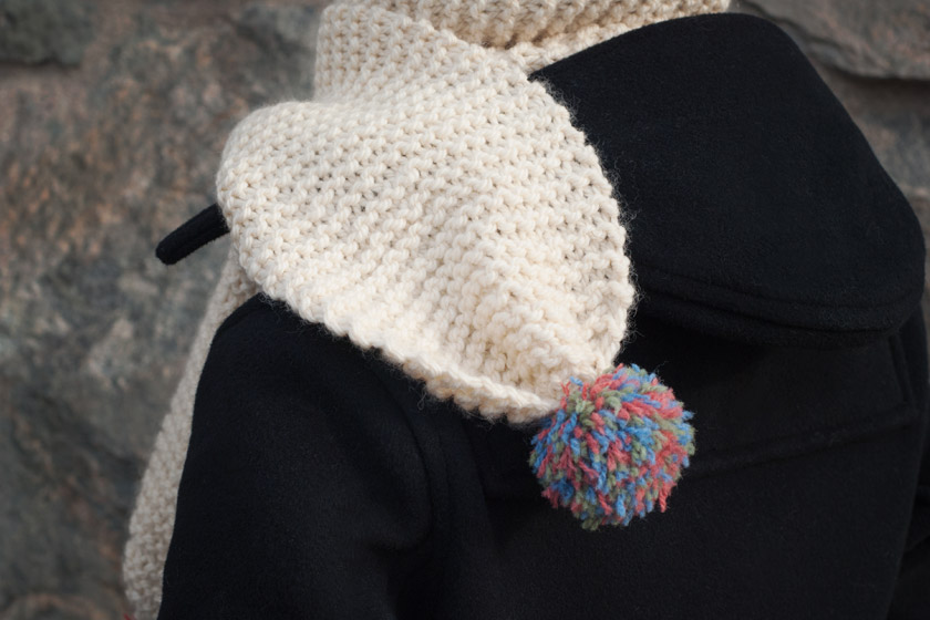 Knitted pompom scarf on shoulder