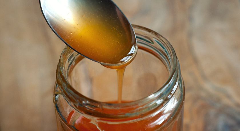 Rosehip syrup dribbling off spoon