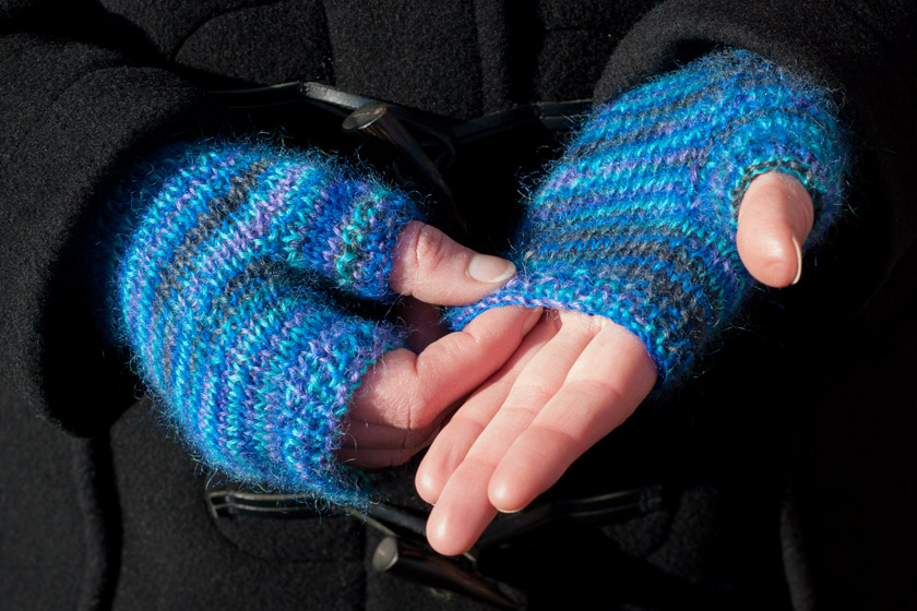 Hands in knitted blue gloves