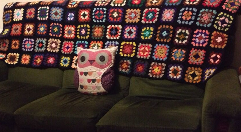 Multi-coloured granny square blanket on sofa