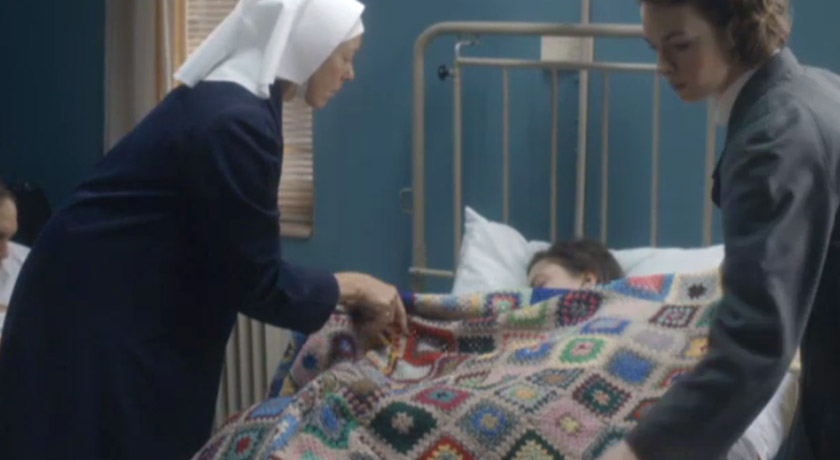 Nun and widwife placing blanket on a hospital bed in Call The Midwife