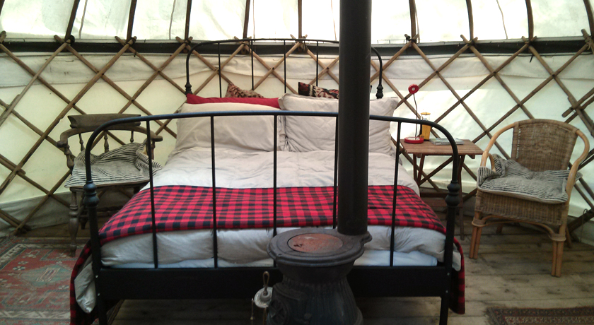Double bed and wood burner in yurt