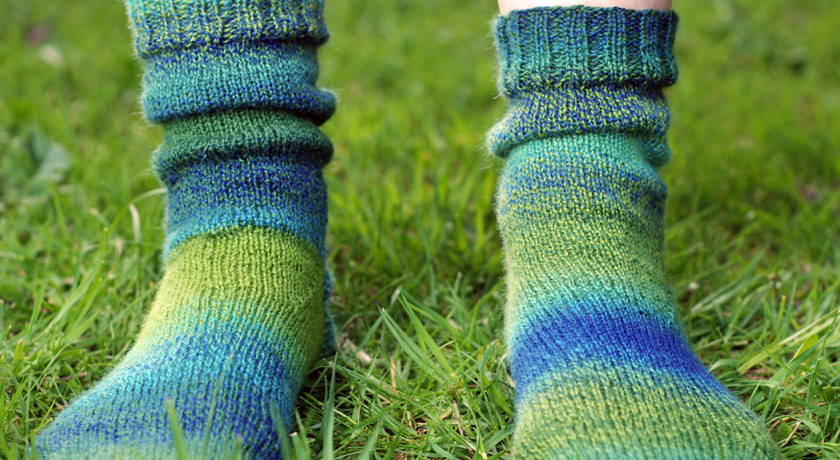 Green and blue knitted socks on grass