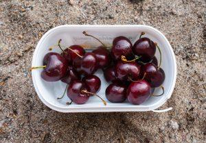 Pot of cherries on sand