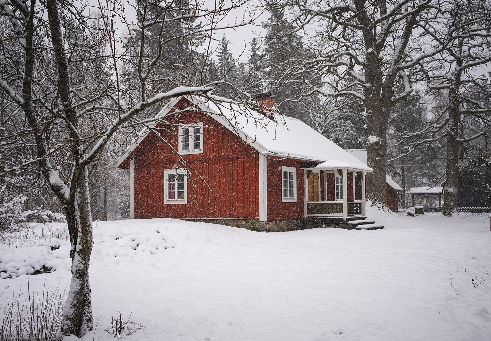 Red wooden house in snow