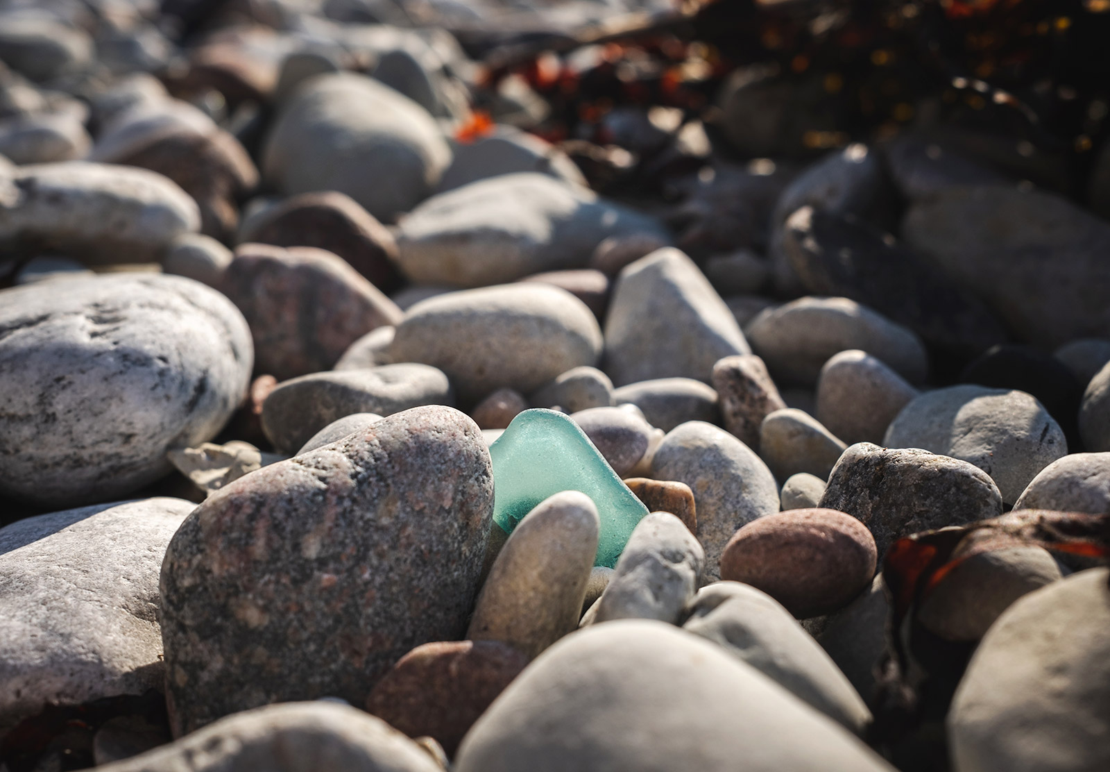 Turquoise glass on pebbles