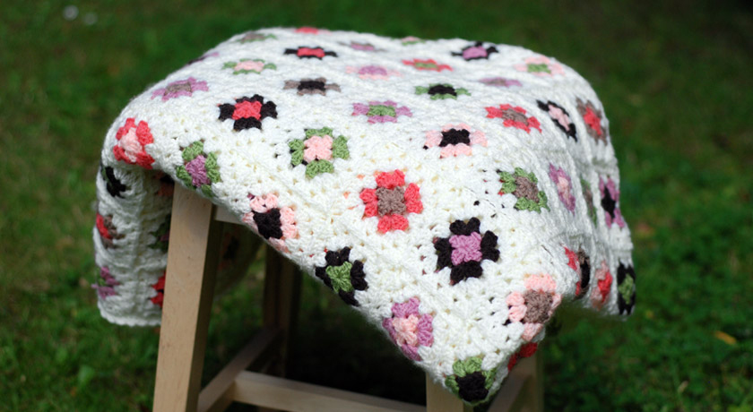 Cream crochet blanket on a stool