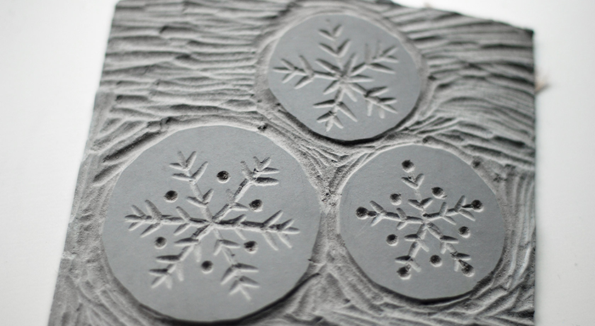 3 snowflakes cut from lino