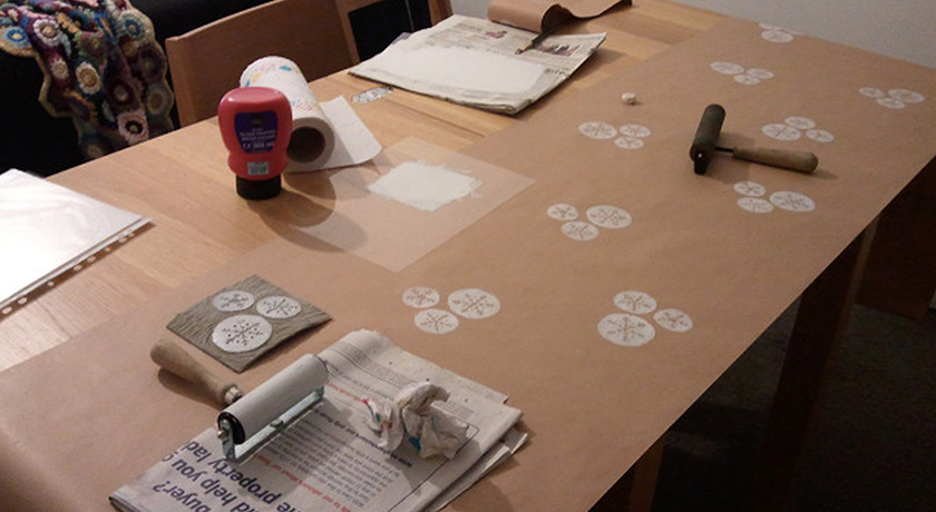 Brown paper being hand printed with white ink