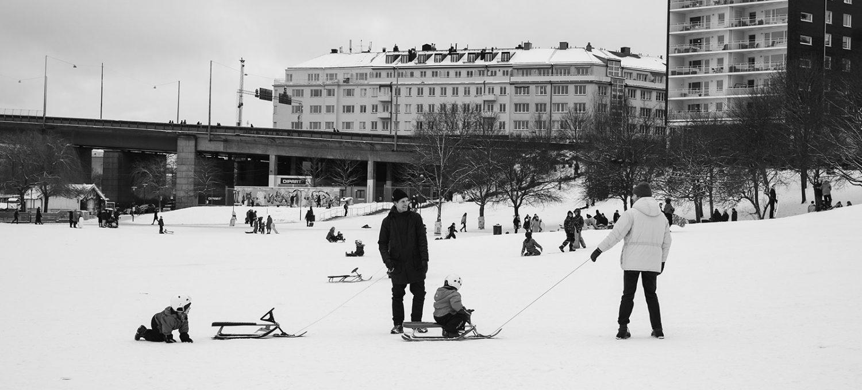 Parents pulling children on sledges