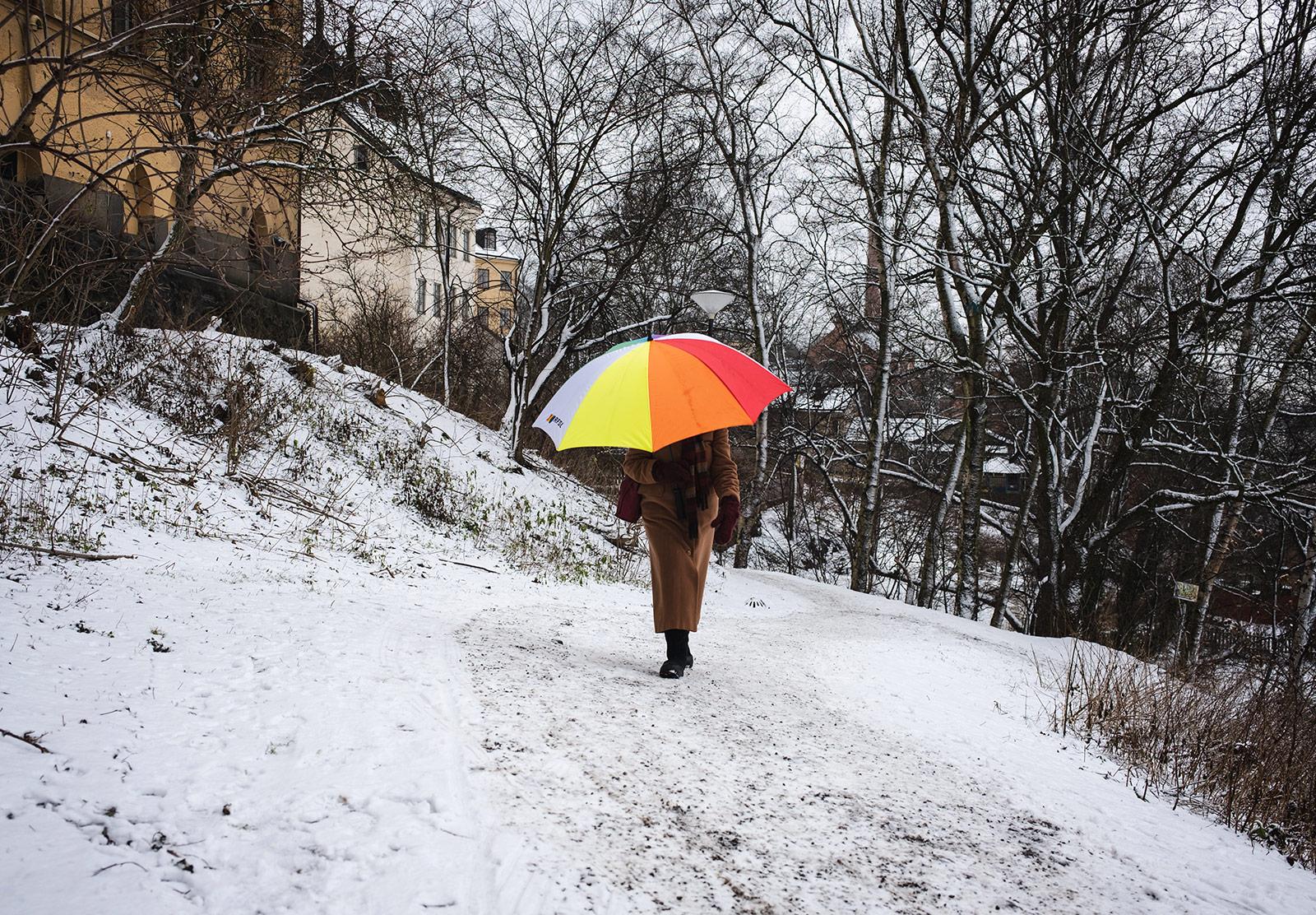 Woman carrying bright umbrella