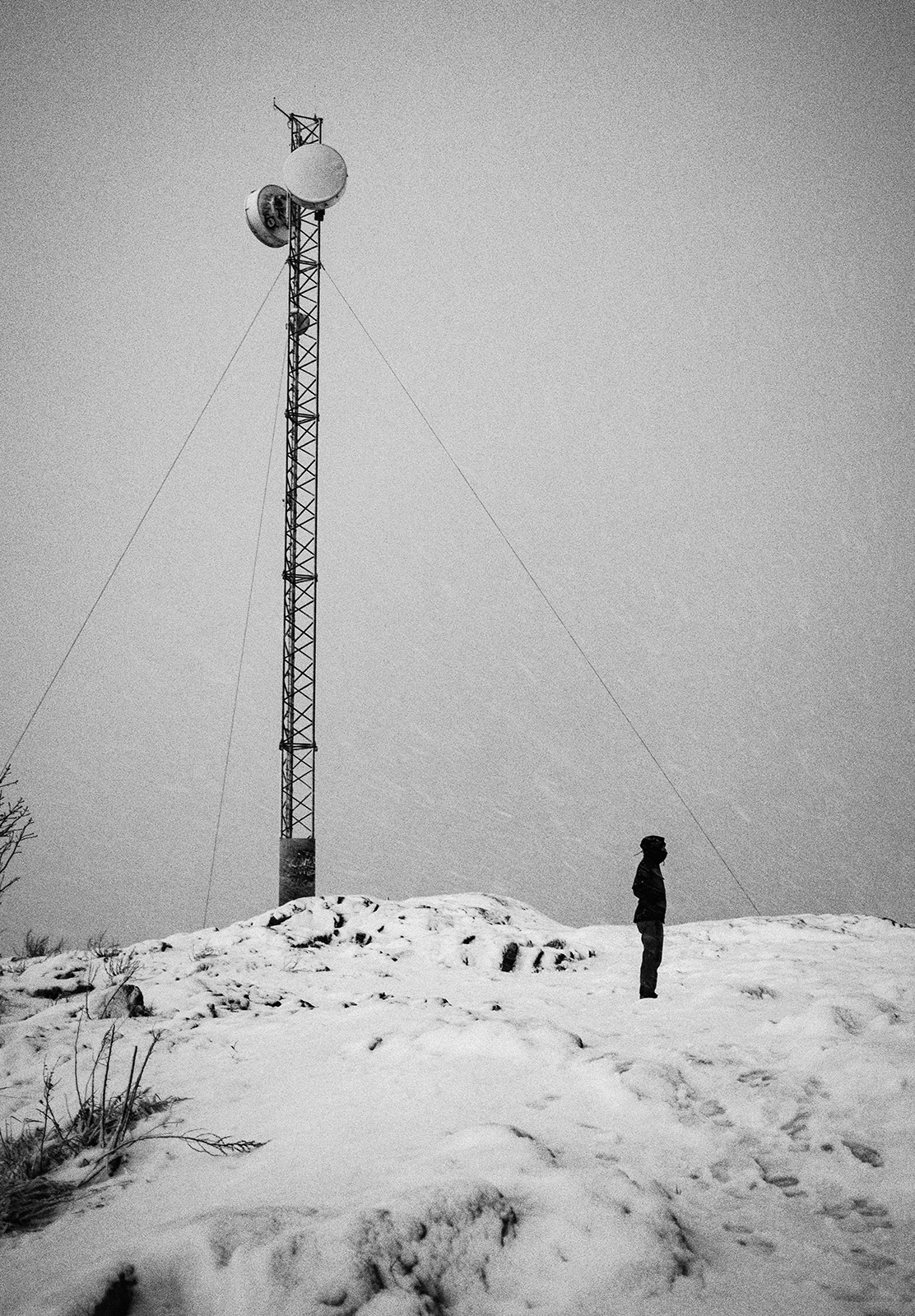 Man stood in snow next to mast