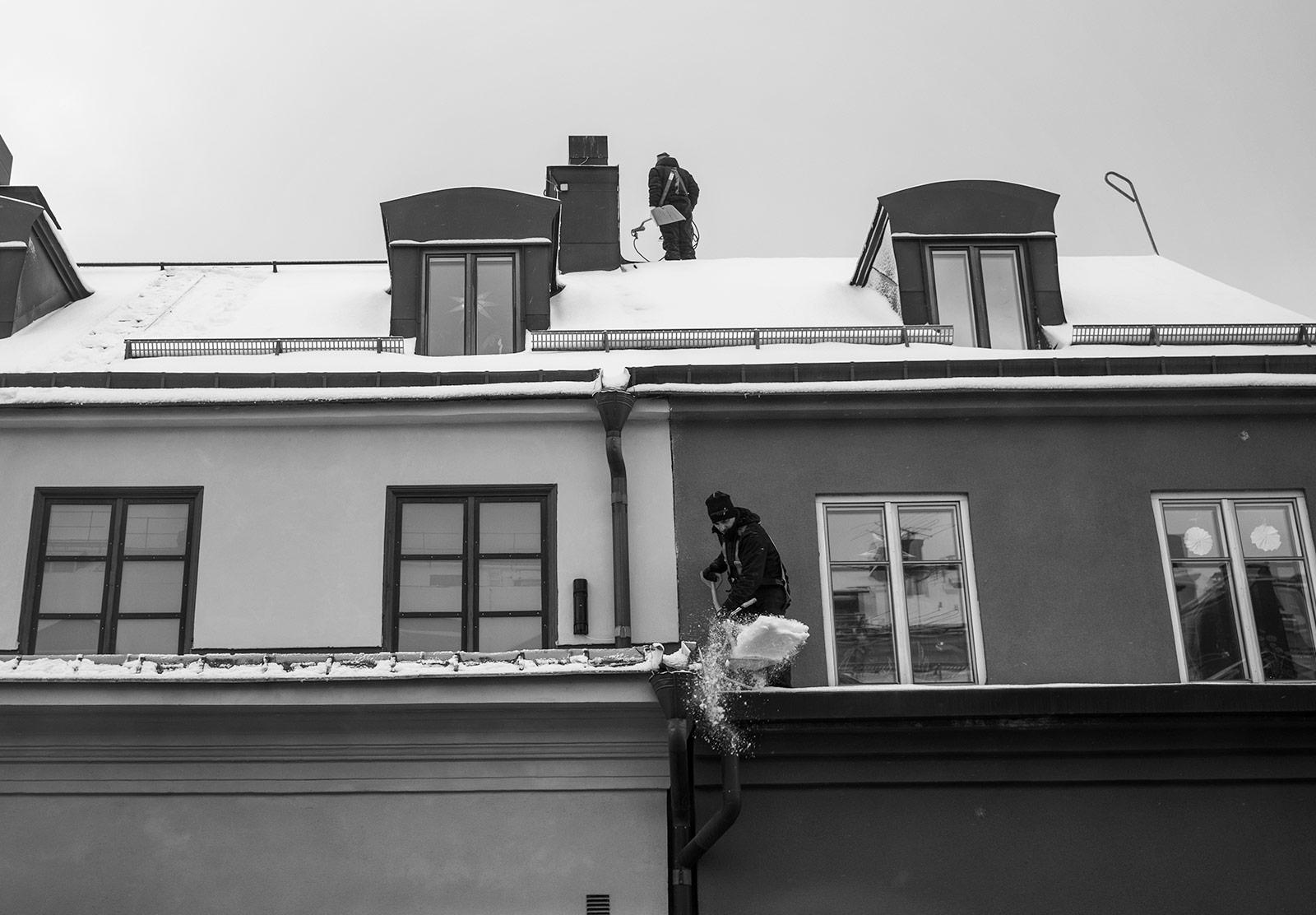 Men shovelling snow off roof