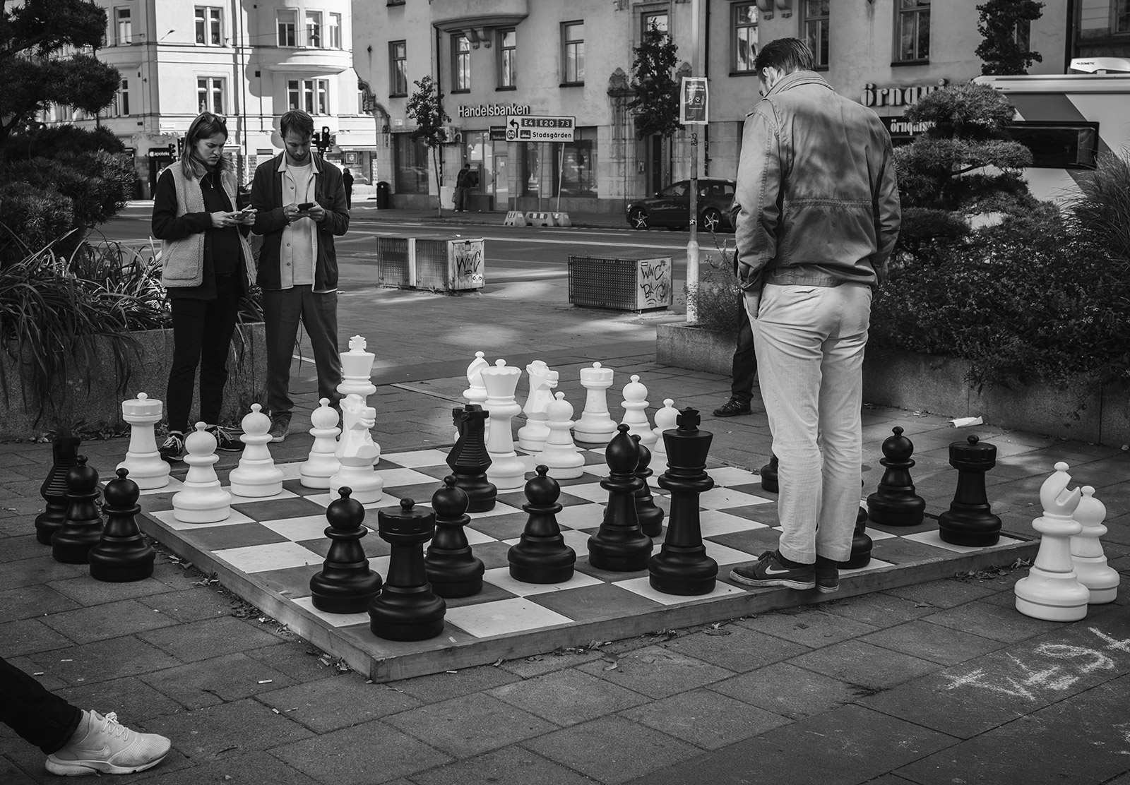 People standing at giant chess board