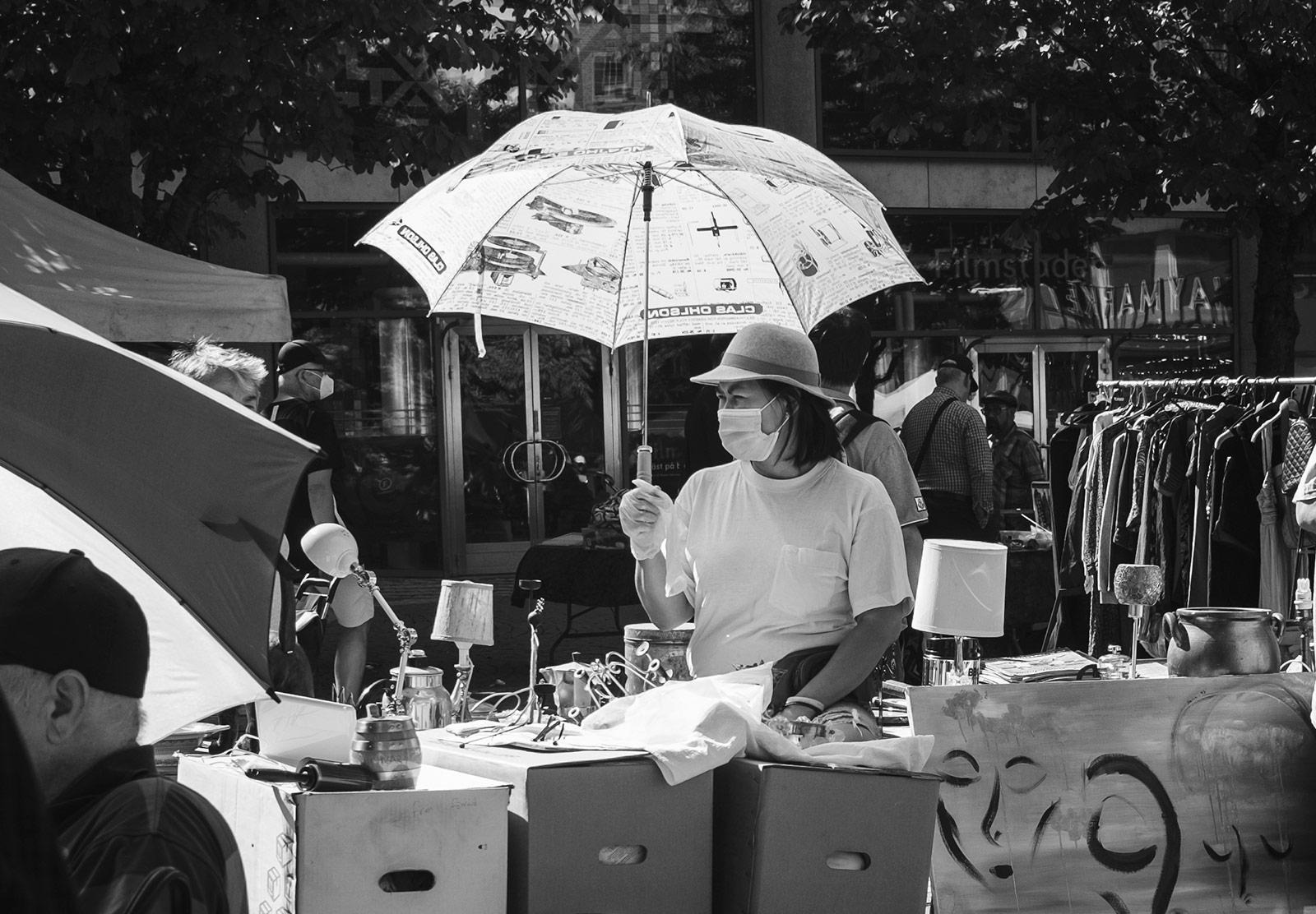 Woman in mask under umbrella