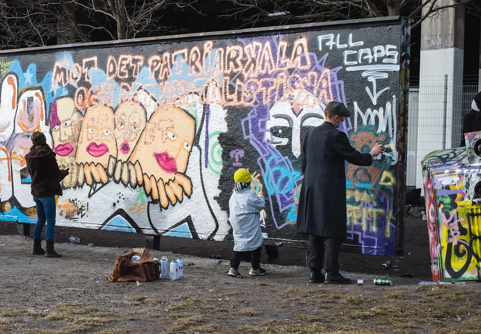 Kid spray painting with parent