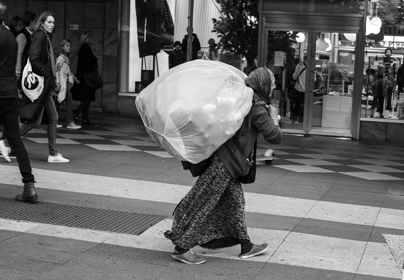Lady carrying big bag of cans