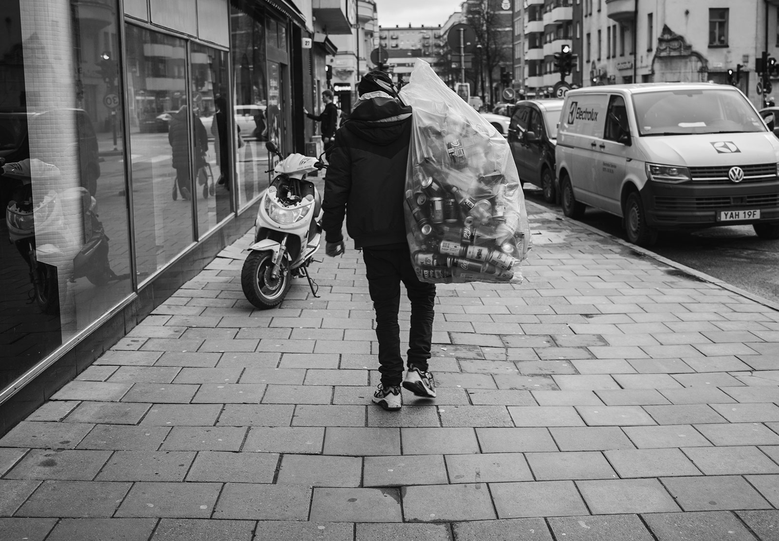 Man carrying bag of bottles and cans