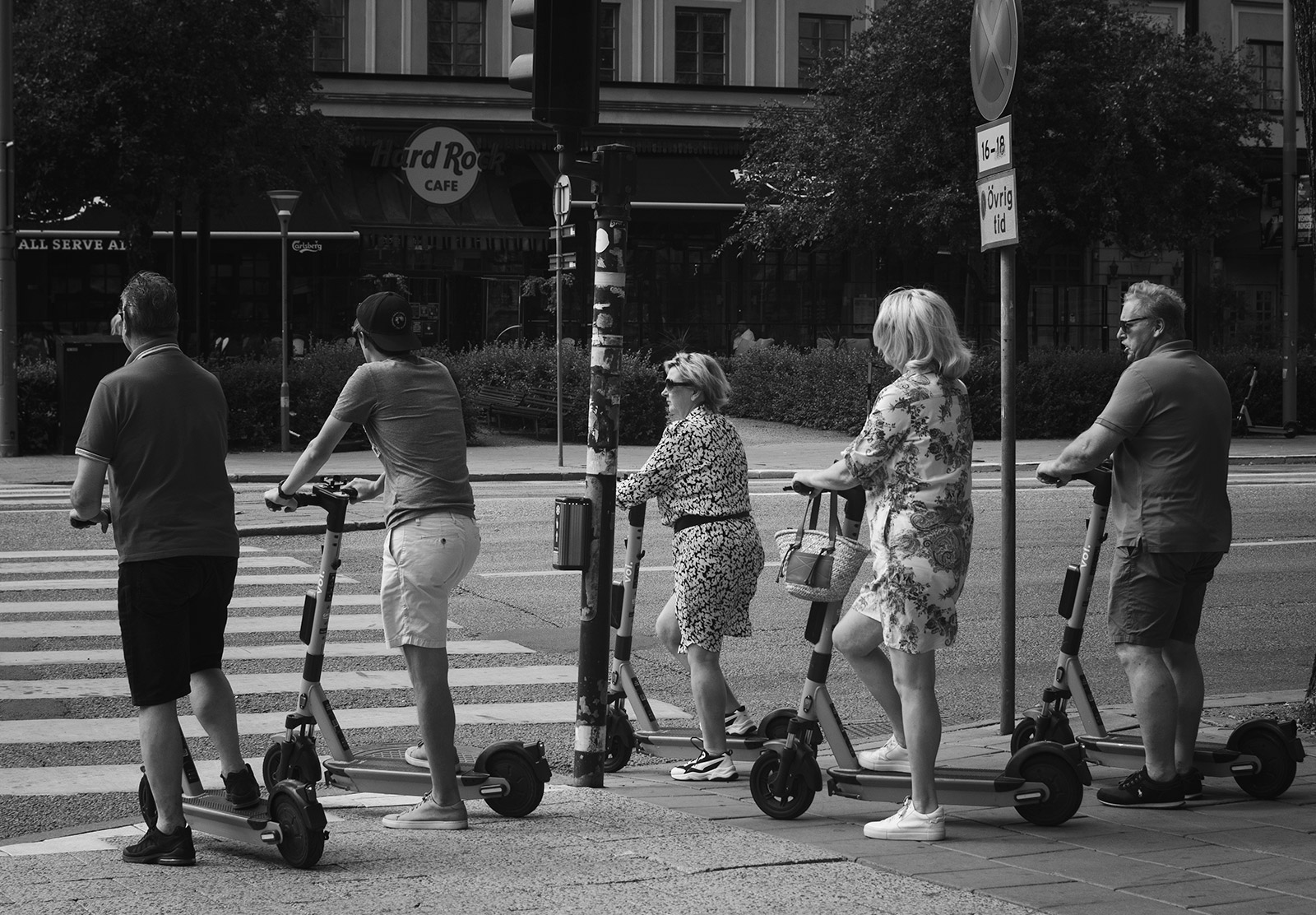 Group of people on scooter at a crossing